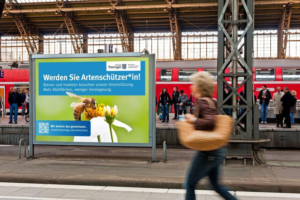 Plakat auf einem Bahnhof mit vielen Menschen, Aufschrift neben Biene auf einer Blüte: Werden Sie Artenschützer
