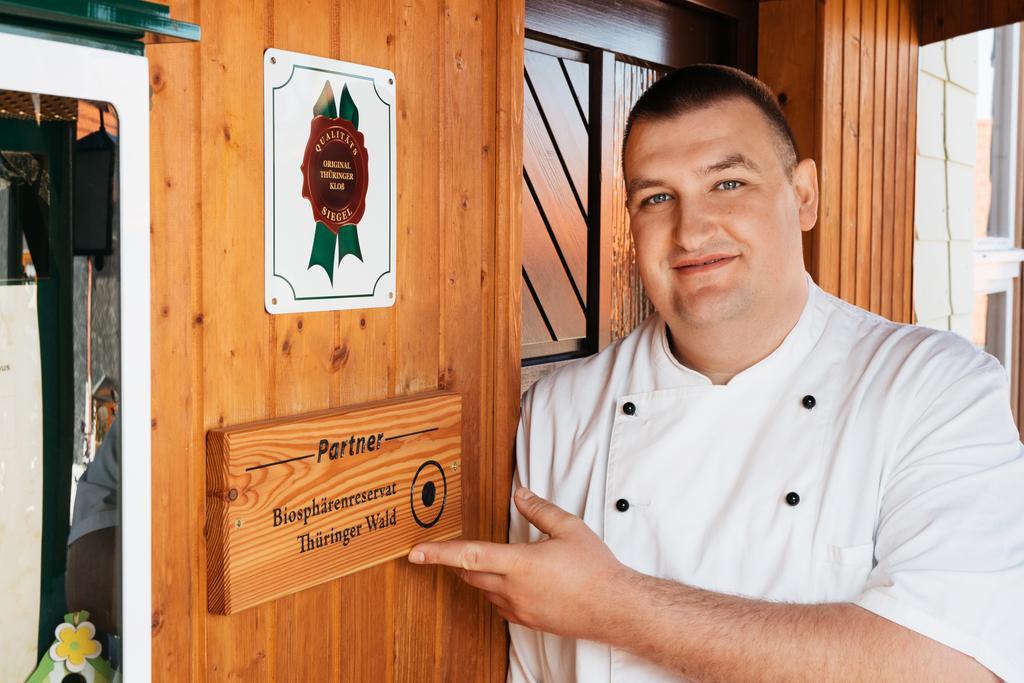 Koch in Berufskleidung am Eingang seines Restaurants