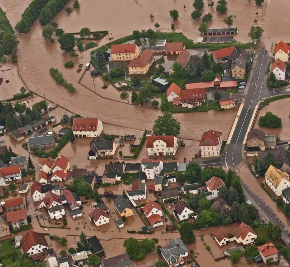 Luftaufnahme eines vom Hochwasser überfluteten Ortes